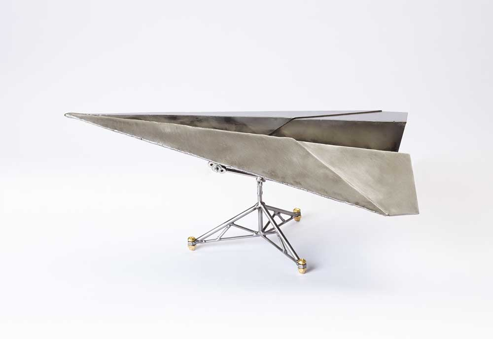 paper plane made of steel on stand